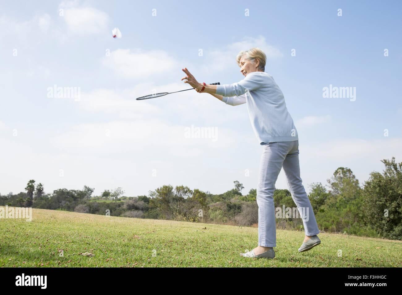 Senior donna riproduzione di badminton in posizione di parcheggio Immagini Stock