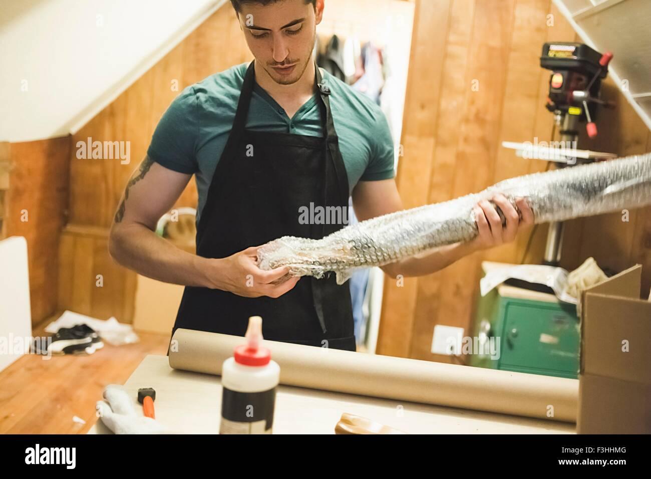 Giovane uomo utilizzando Bubble wrap per preparare il pacco per la consegna Immagini Stock