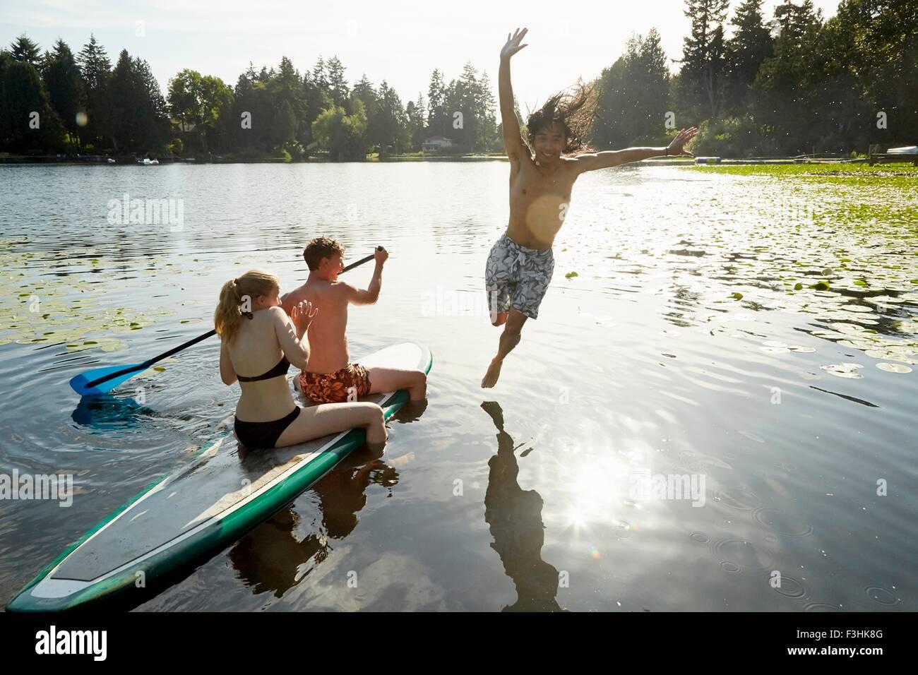 Giovane paddling barca, uomo saltando nel lago, Seattle, Washington, Stati Uniti d'America Foto Stock