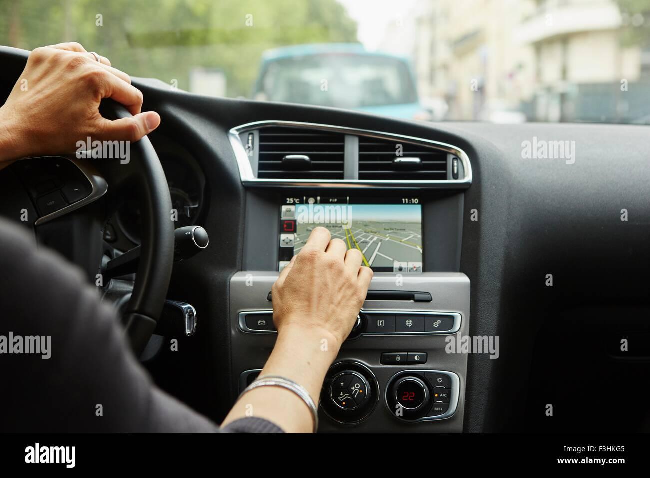 Donna seduta in auto, utilizzando il gps, concentrarsi sulle mani Immagini Stock