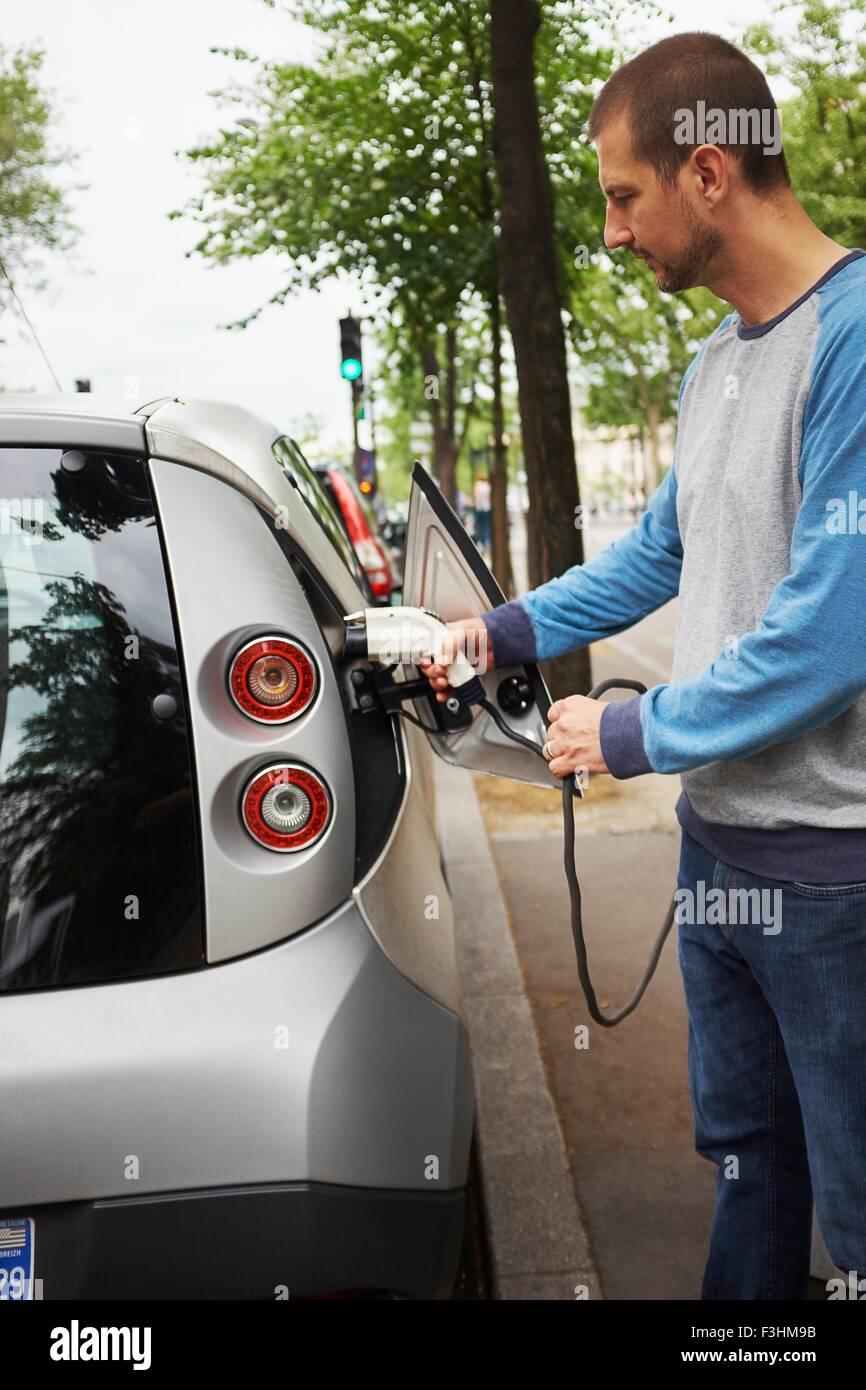 Uomo di ricarica auto elettrica su strada, Parigi, Francia Immagini Stock