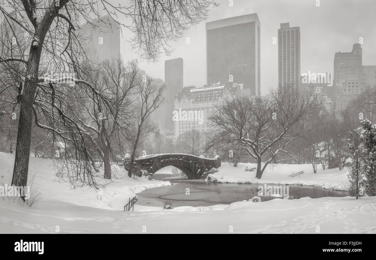 Congelato stagno e forte nevicata nel parco centrale. Gapstow Bridge e Manhattan alta sorge e grattacieli. Inverno Immagini Stock