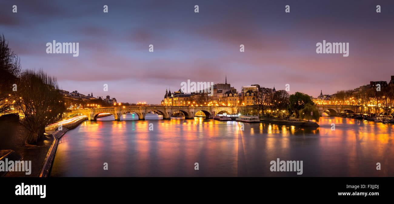 Sunrise nel cuore di Parigi, in Francia con Ile de la Cite e Pont Neuf. Un tranquillo Fiume Senna riflette le luci Immagini Stock