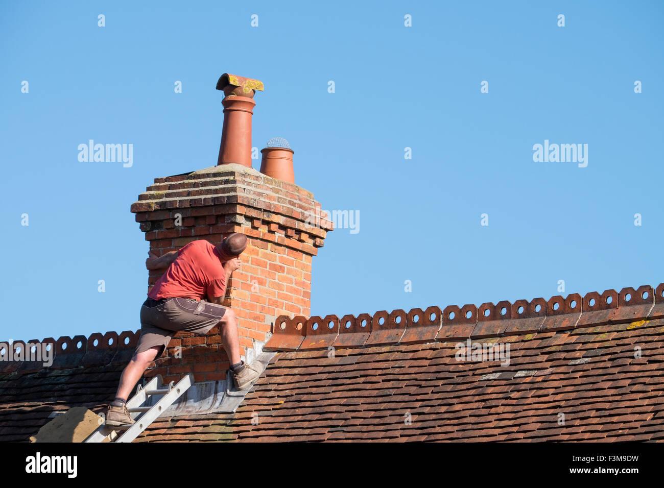 Un uomo su un tetto di ispezionare un camino per la riparazione Immagini Stock