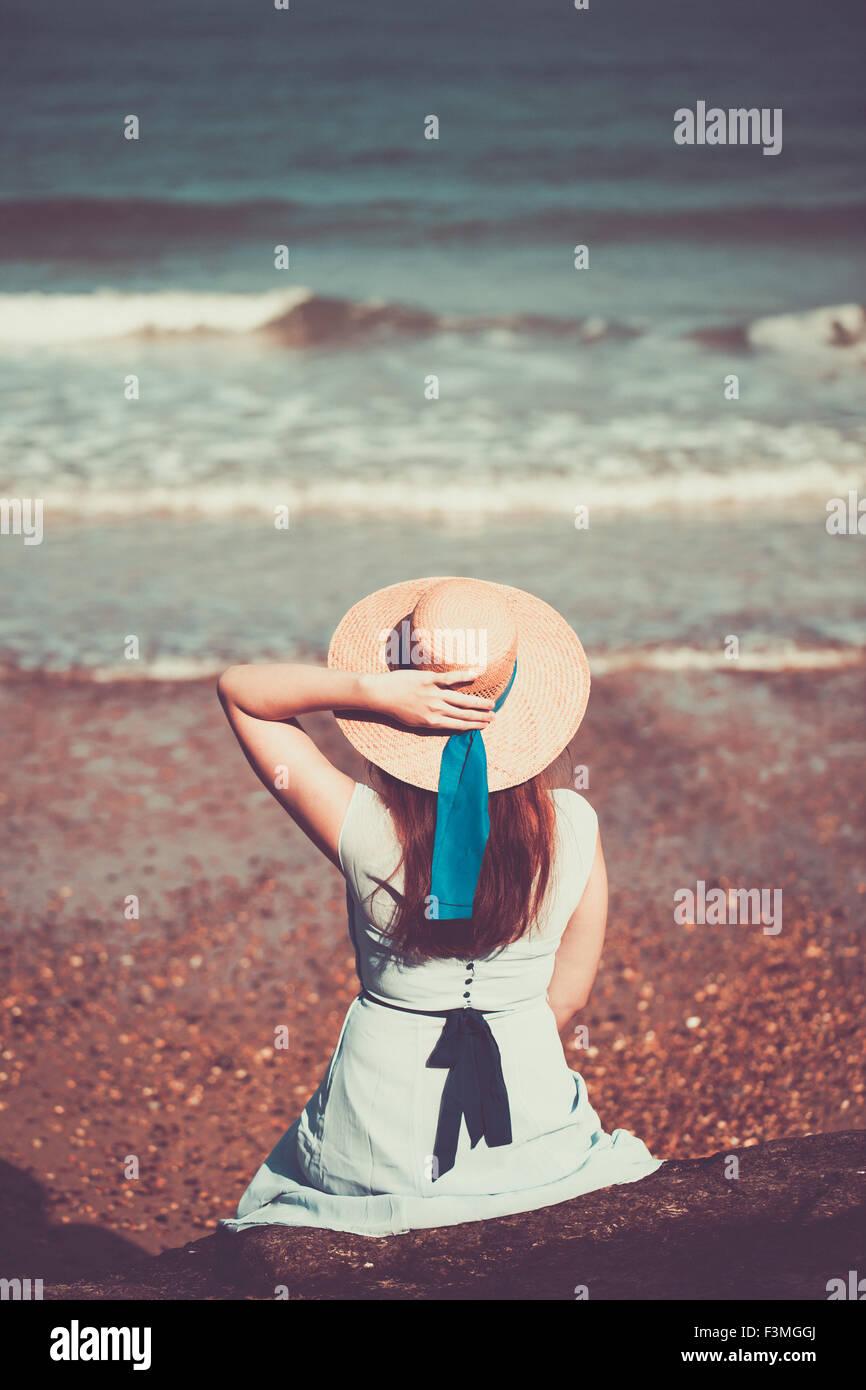 Giovane e bella ragazza storico seduto sulla spiaggia in un vestito blu e indossando un cappello di paglia Immagini Stock