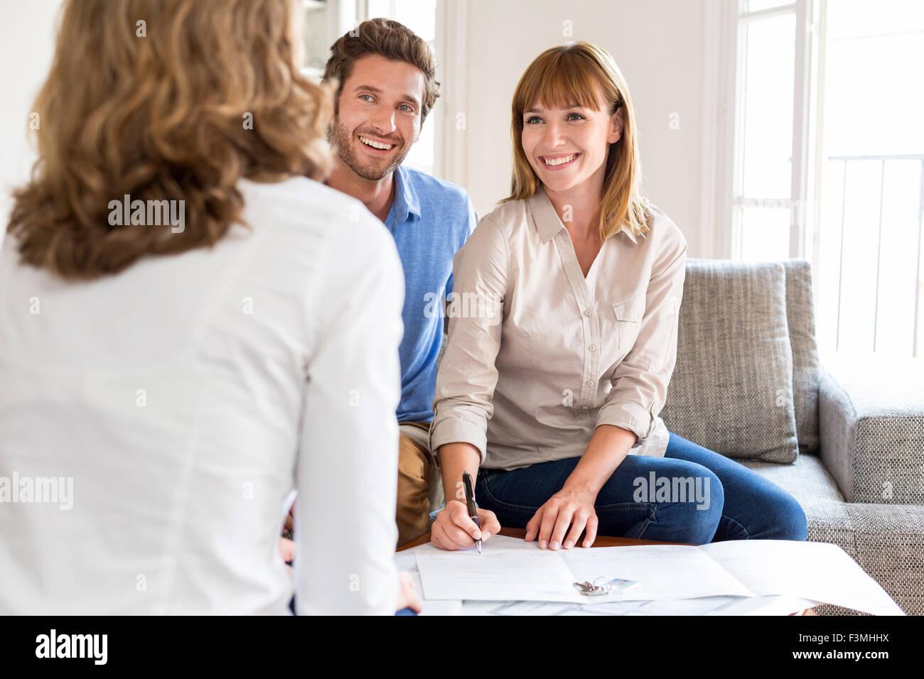 Coppia giovane proprietari incontro agente immobiliare per la casa degli investimenti. La firma di un contratto. Immagini Stock