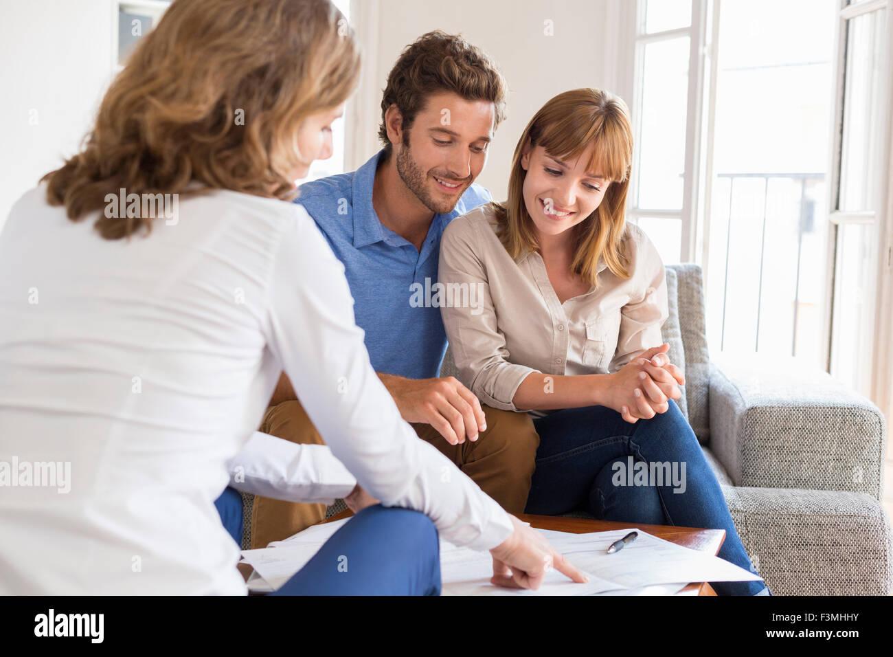 Agente immobiliare presentando un contratto per la casa di investimenti per i futuri proprietari giovane Immagini Stock