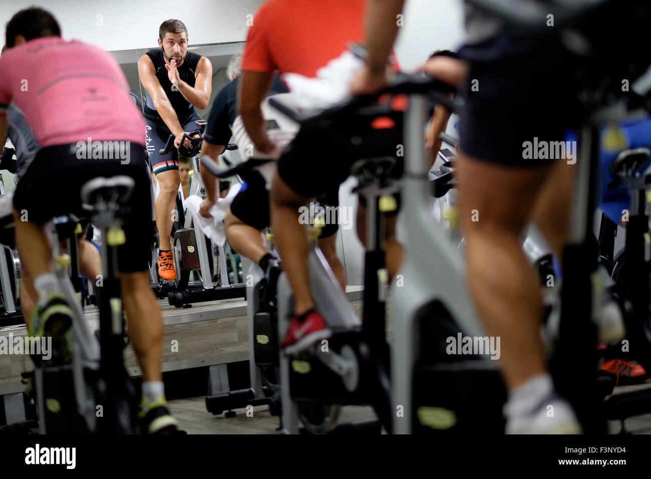 Istruttore di Fitness di fronte a persone di equitazione bicicletta stazionaria durante una lezione di spinning Foto Stock