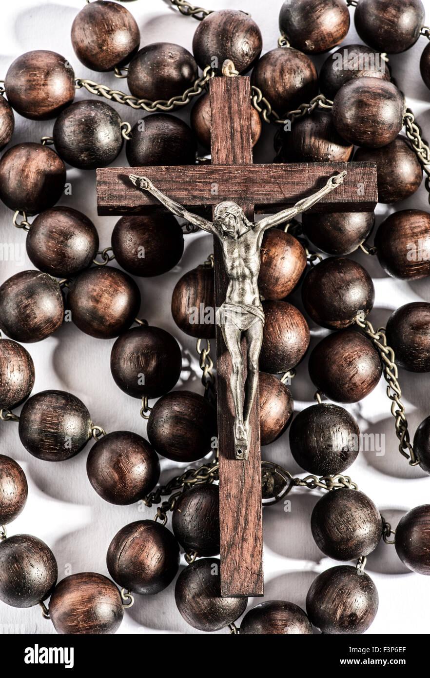 Rosario in legno con un crocifisso raffigurante un Cristo crocifisso su una croce di legno Immagini Stock