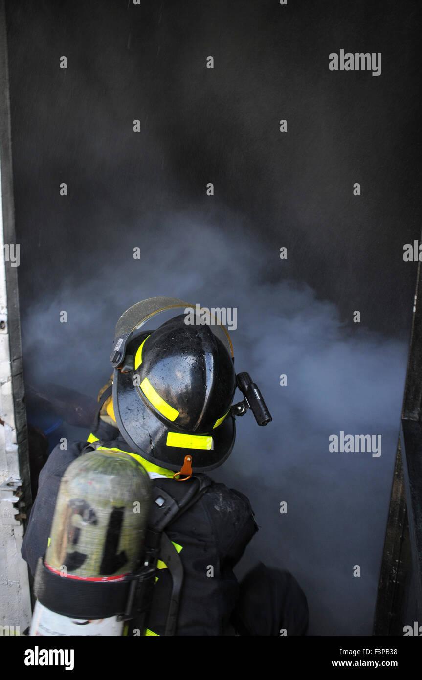 I vigili del fuoco con apparecchiature protettive in una piena di fumo camera Immagini Stock