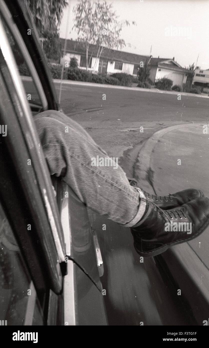 c0c40829b142 Un punker punk rocker indossando doc marten stivali da combattimento pende  le gambe di una vettura ruotando di un angolo in un tratto suburbano home  ...