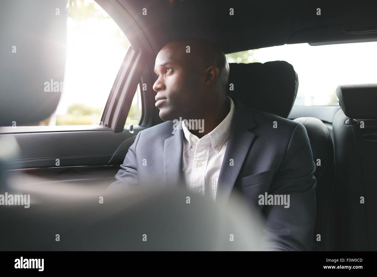 Giovane africano uomo d'affari in viaggio per lavoro in auto di lusso sul sedile posteriore di guardare fuori Immagini Stock