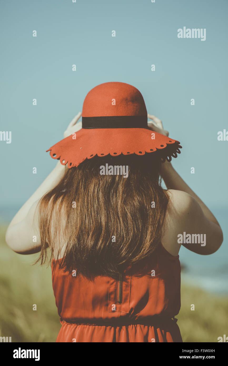 Giovane donna in un abito rosso sulla spiaggia Immagini Stock