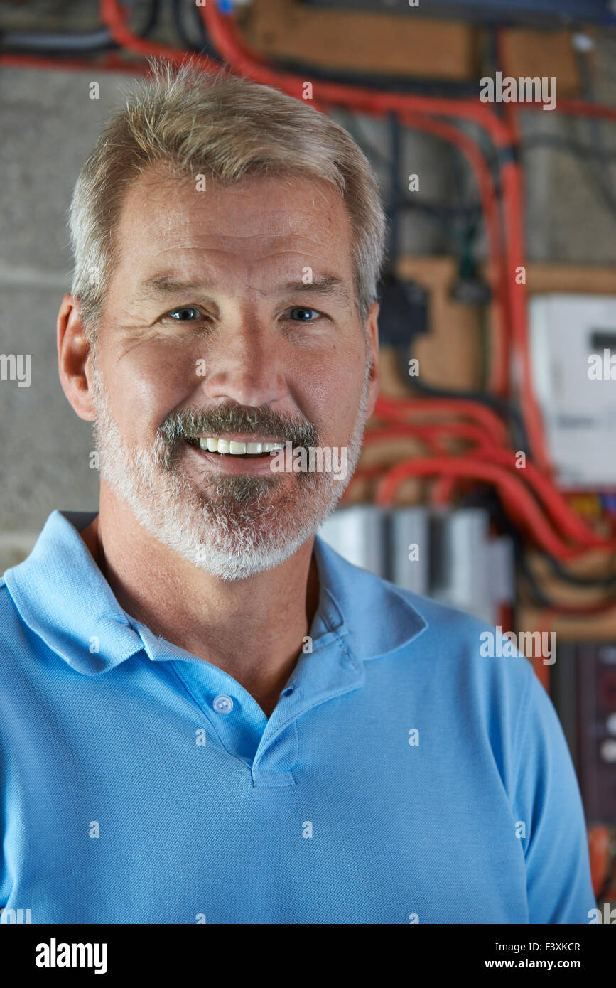 Ritratto di elettricista in piedi accanto alla basetta fusibile Immagini Stock