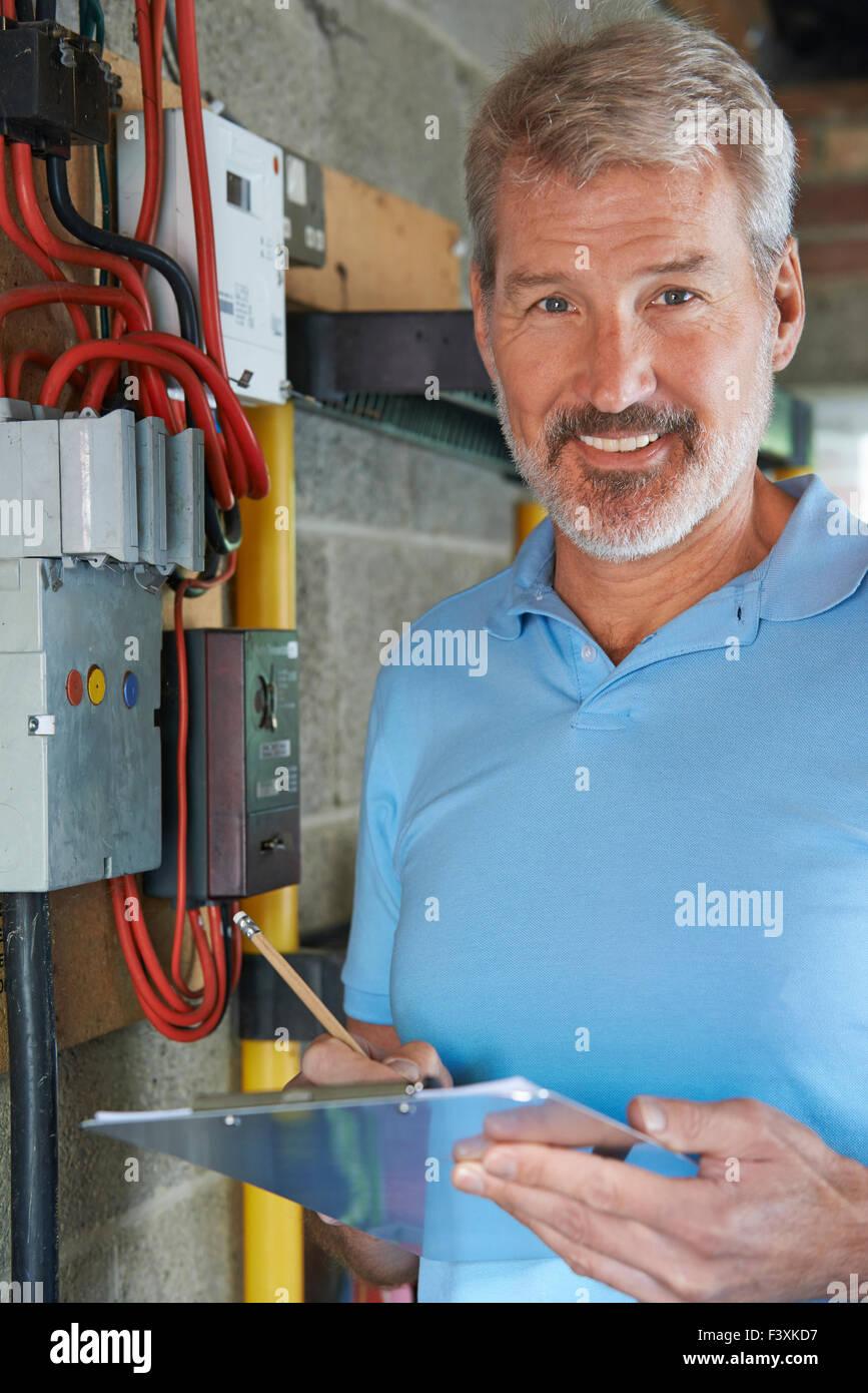 Ritratto di elettricista in piedi accanto alla scheda fusibili Immagini Stock