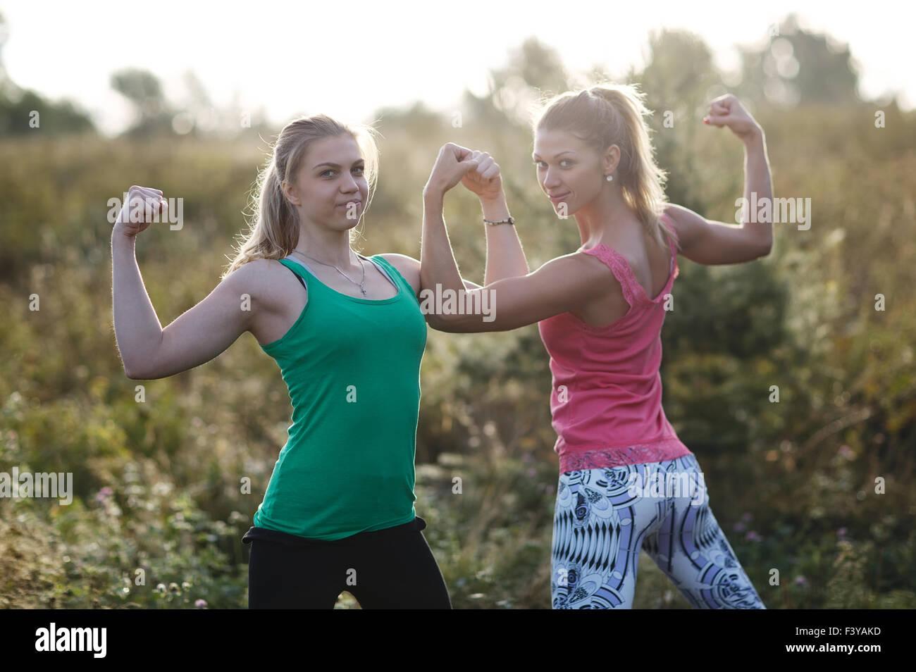 Due ragazze atletica flettendo i loro muscoli del braccio Immagini Stock