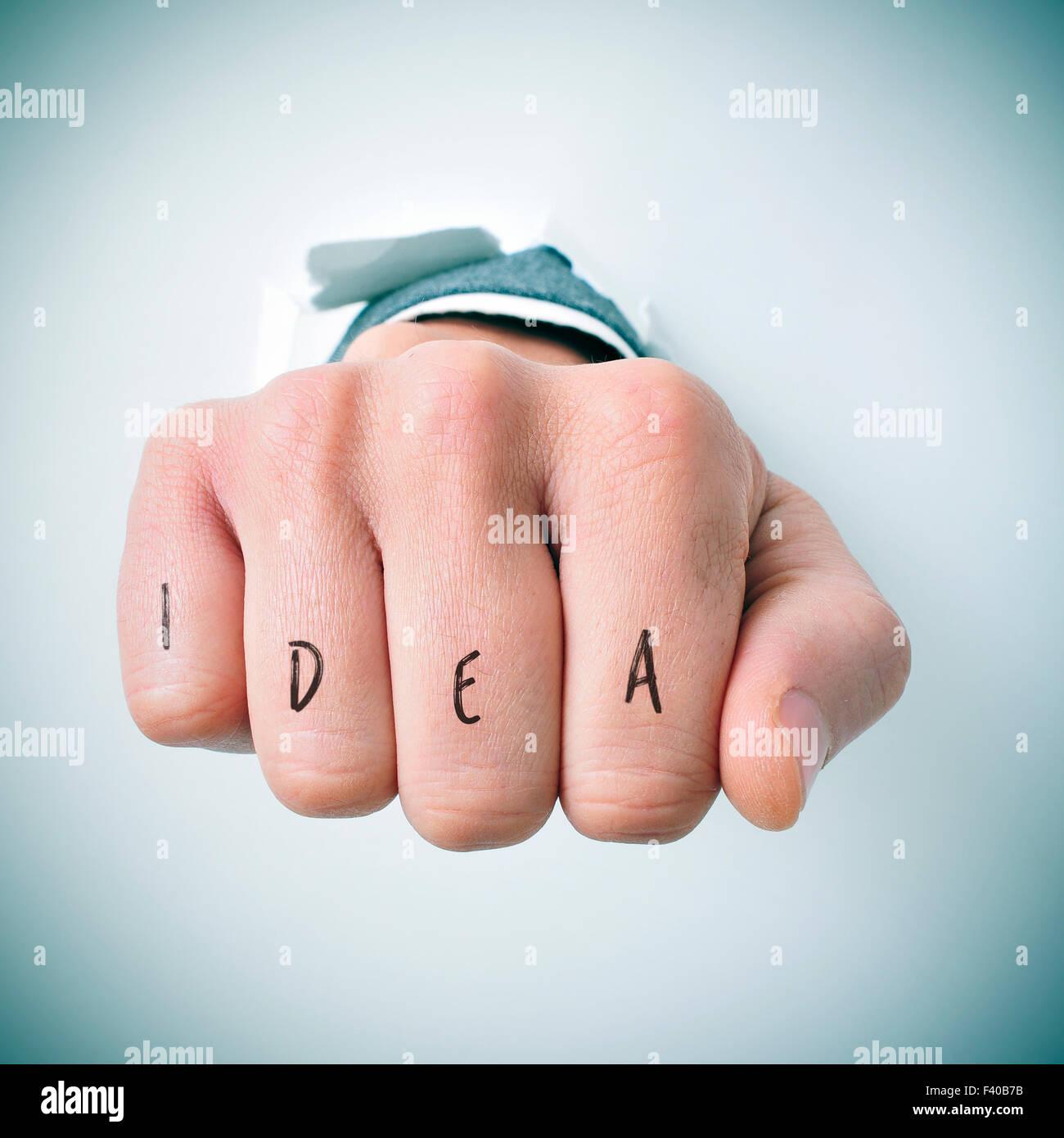 Un giovane imprenditore si rompe attraverso una parete con il pugno e la parola idea scritto nel suo knuckles Immagini Stock