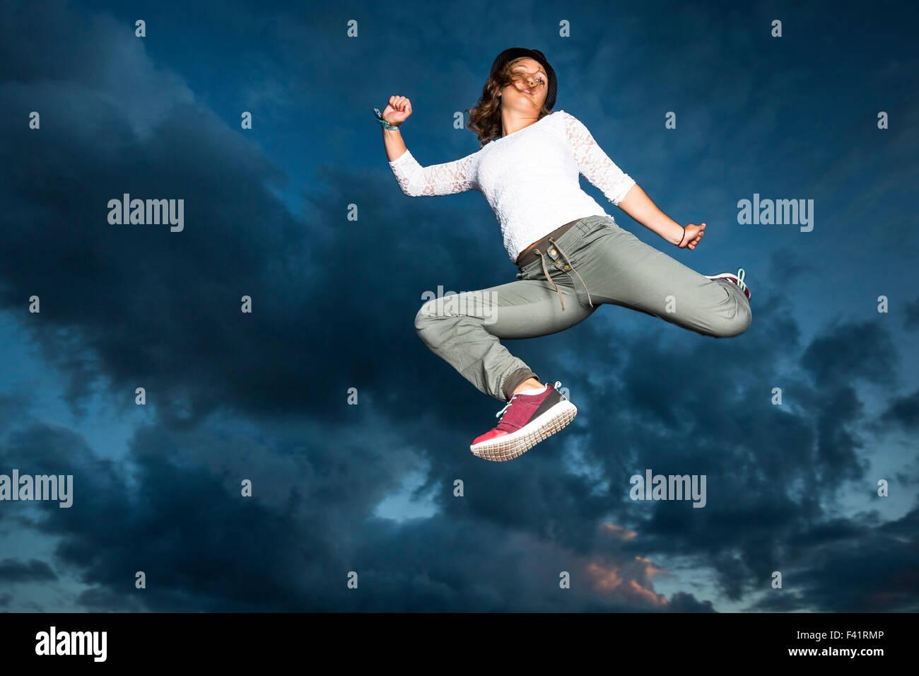 Giovane donna, 19 anni, saltando, a mezz aria contro il cielo di sera Immagini Stock