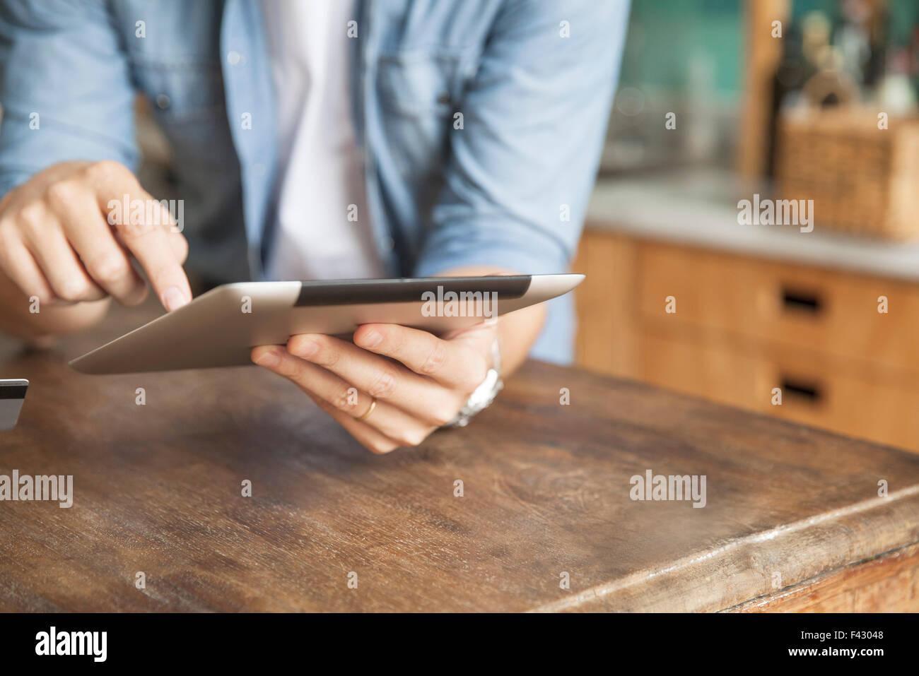 Uomo con dispositivo wireless a casa Immagini Stock