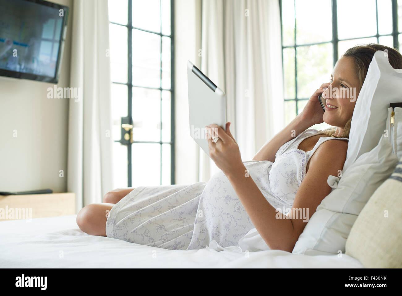 Donna incinta relax nel letto, utilizzando tavoletta digitale e chattare su telefono cellulare Immagini Stock