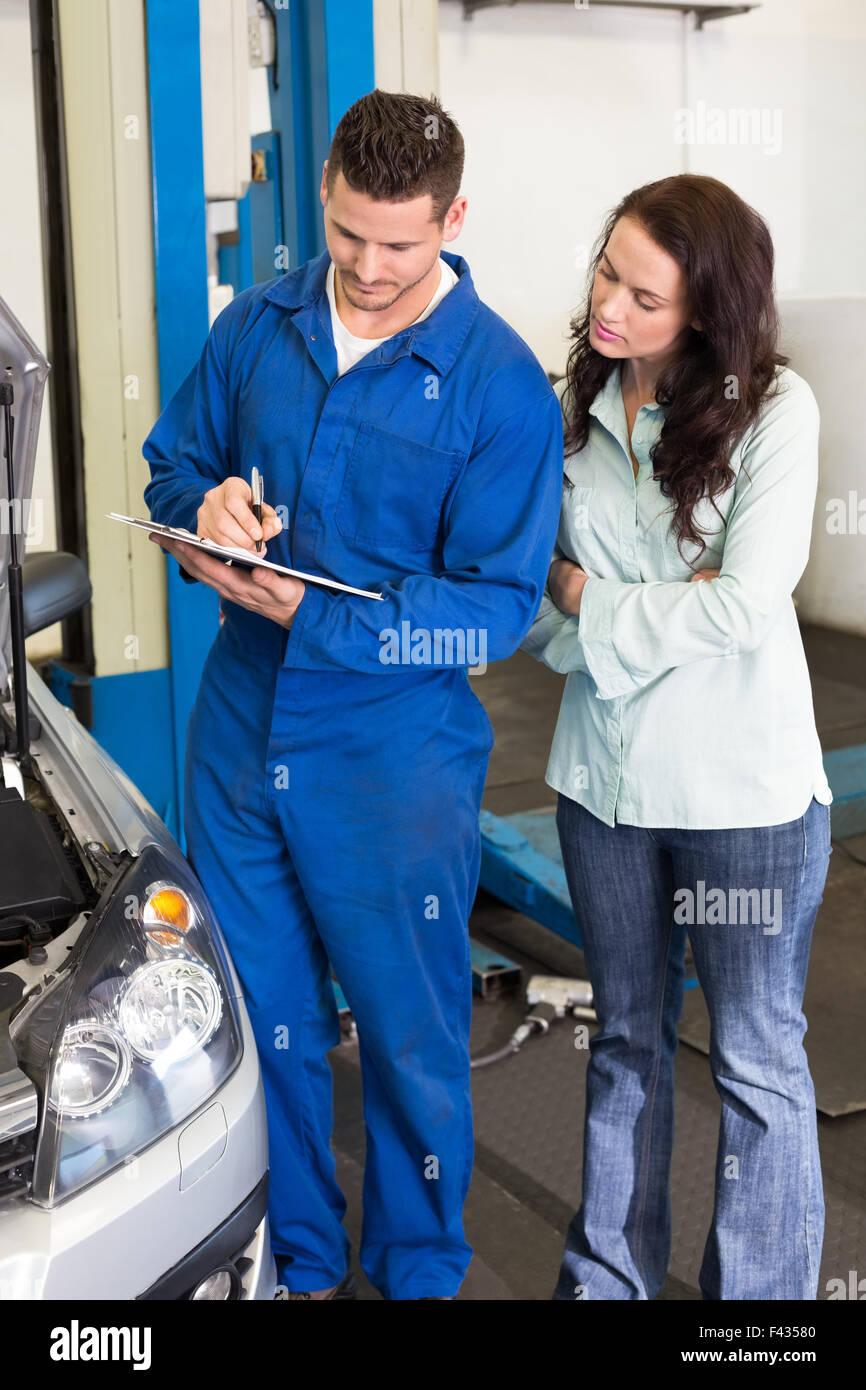 Meccanico e il cliente insieme permanente Immagini Stock