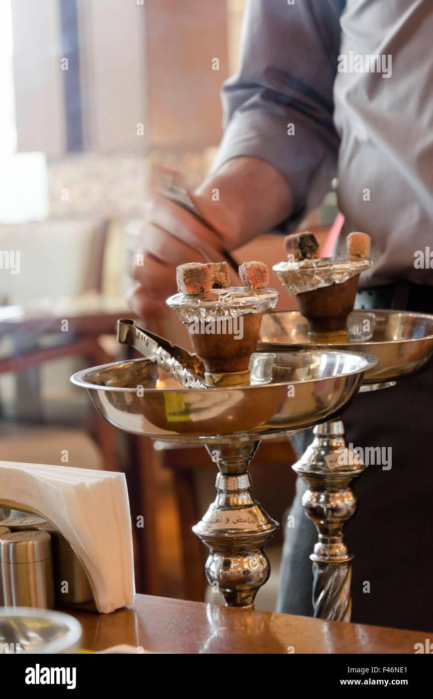 Preparare il shisha, aka nargile o hookah presso un ristorante ponendo i carboni di legna sulla parte superiore. Immagini Stock