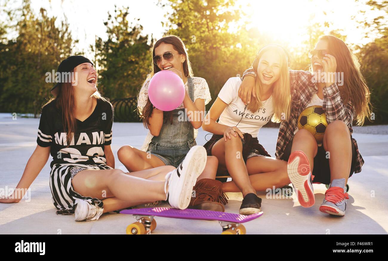 Amici divertendosi in un parco con skateboard e occhiali da sole Immagini Stock