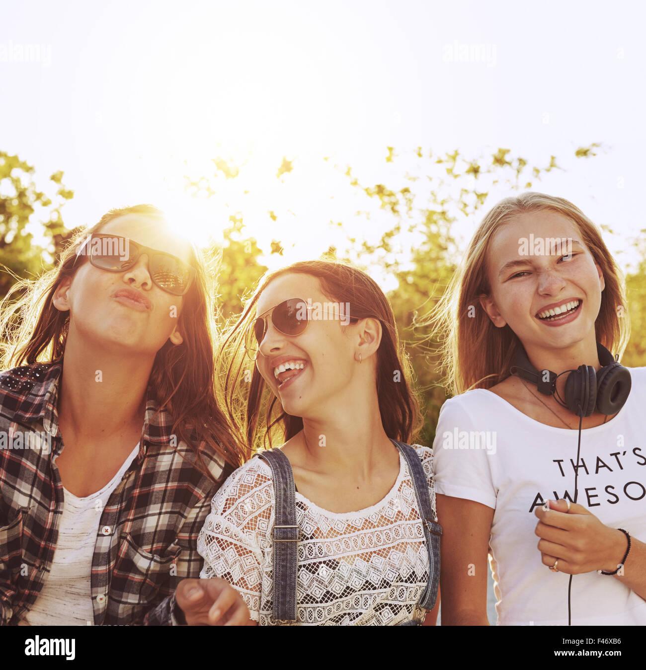 Tre ragazze adolescenti ridere appendere fuori in un giorno di estate Foto Stock