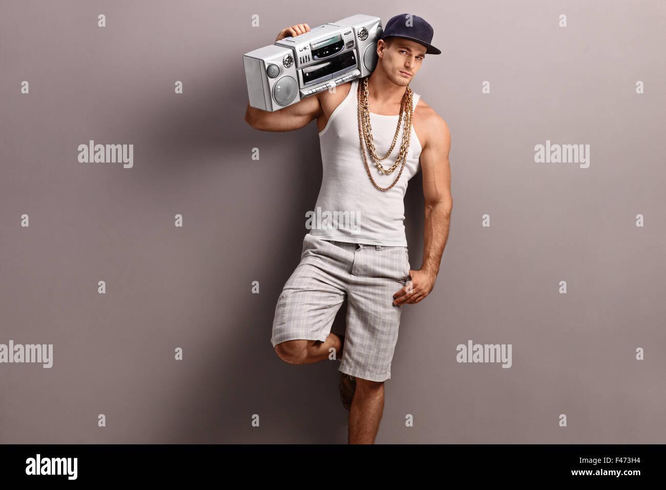 Giovane uomo in hip-hop vestiti portando un ghetto blaster sulla sua spalla  e appoggiata 94292fe9bac0