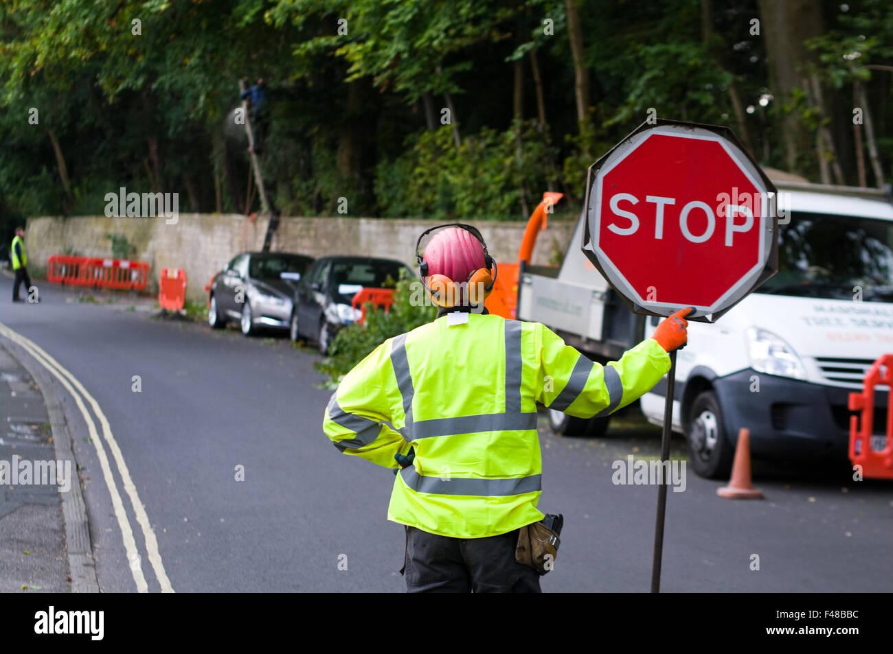 Un uomo in un GIUBBETTO ALTA VISIBILITA detiene una 'STOP' traffico segno di controllo per il controllo Immagini Stock