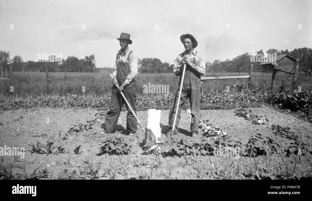Due agricoltori tendente ad un giardino durante la Grande Depressione. tute da giardinaggio agricoltura cibo crescente Immagini Stock