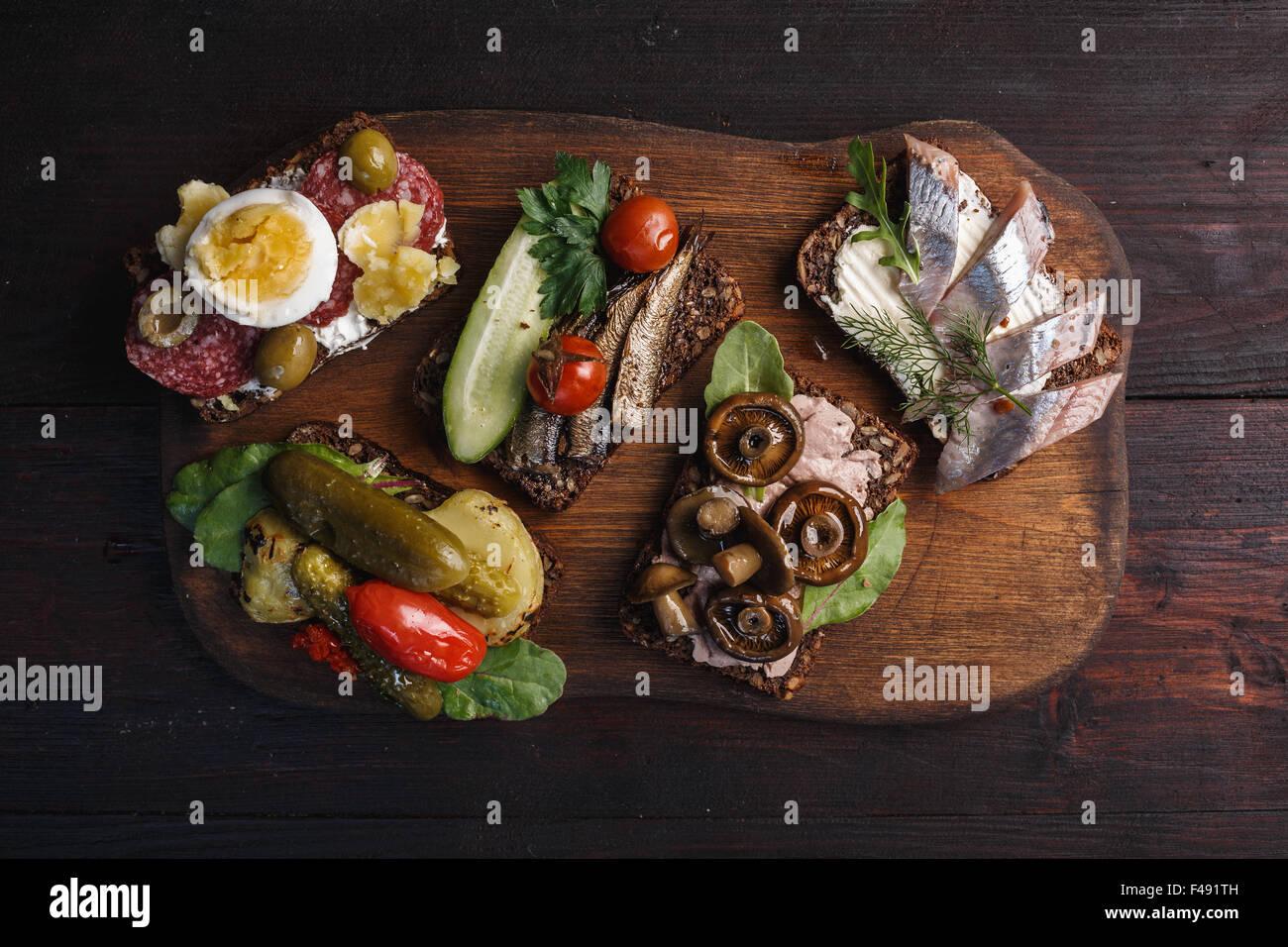 Varietà di aprire panini di dense imburrato, scuro pane di segale con diversi condimenti. Smorrebrods danese Immagini Stock