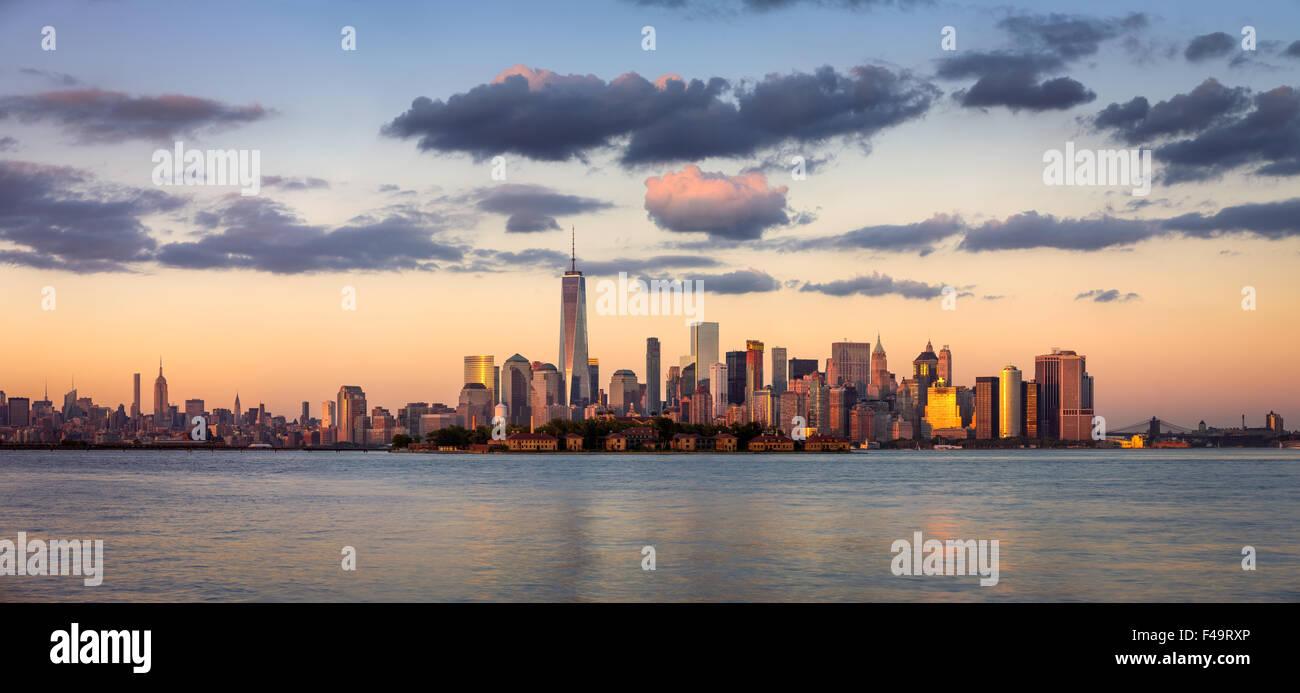La parte inferiore di Manhattan grattacieli, il quartiere finanziario e Ellis Island panorama al tramonto, New York City, Stati Uniti d'America Foto Stock