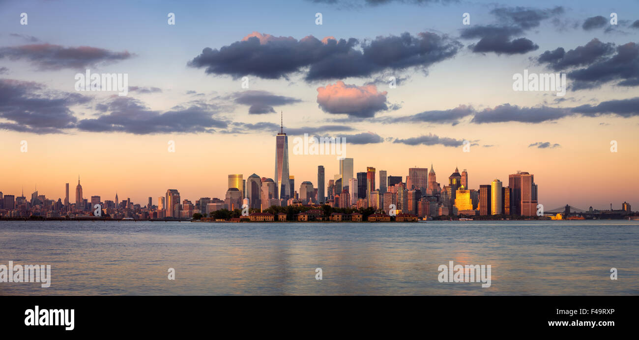 La parte inferiore di Manhattan grattacieli, il quartiere finanziario e Ellis Island panorama al tramonto, New York Foto Stock