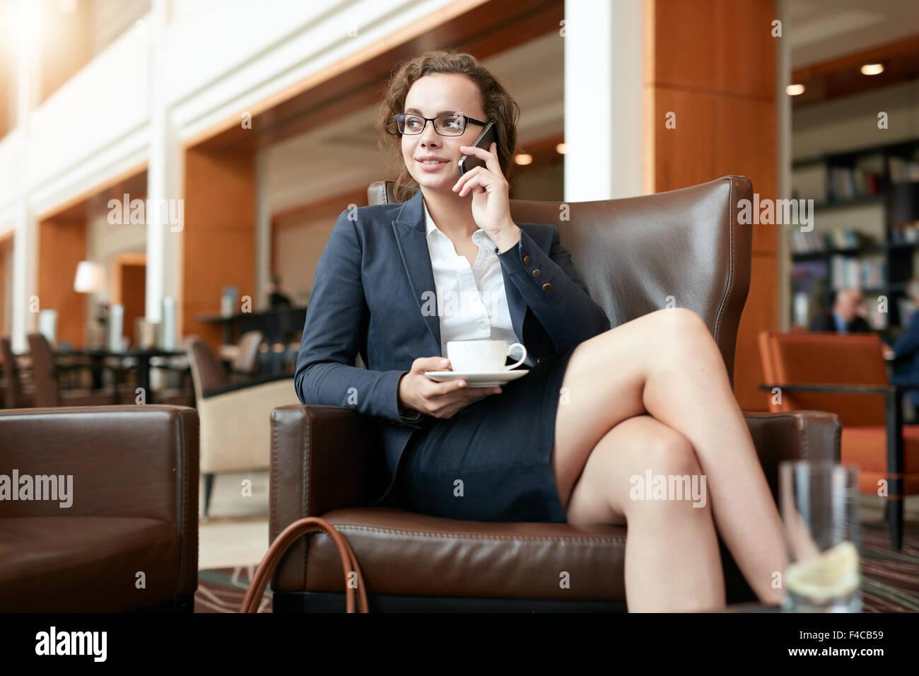 Ritratto di felice giovane imprenditrice seduta in cafe parlando al telefono cellulare. Executive femmina con tazza Immagini Stock