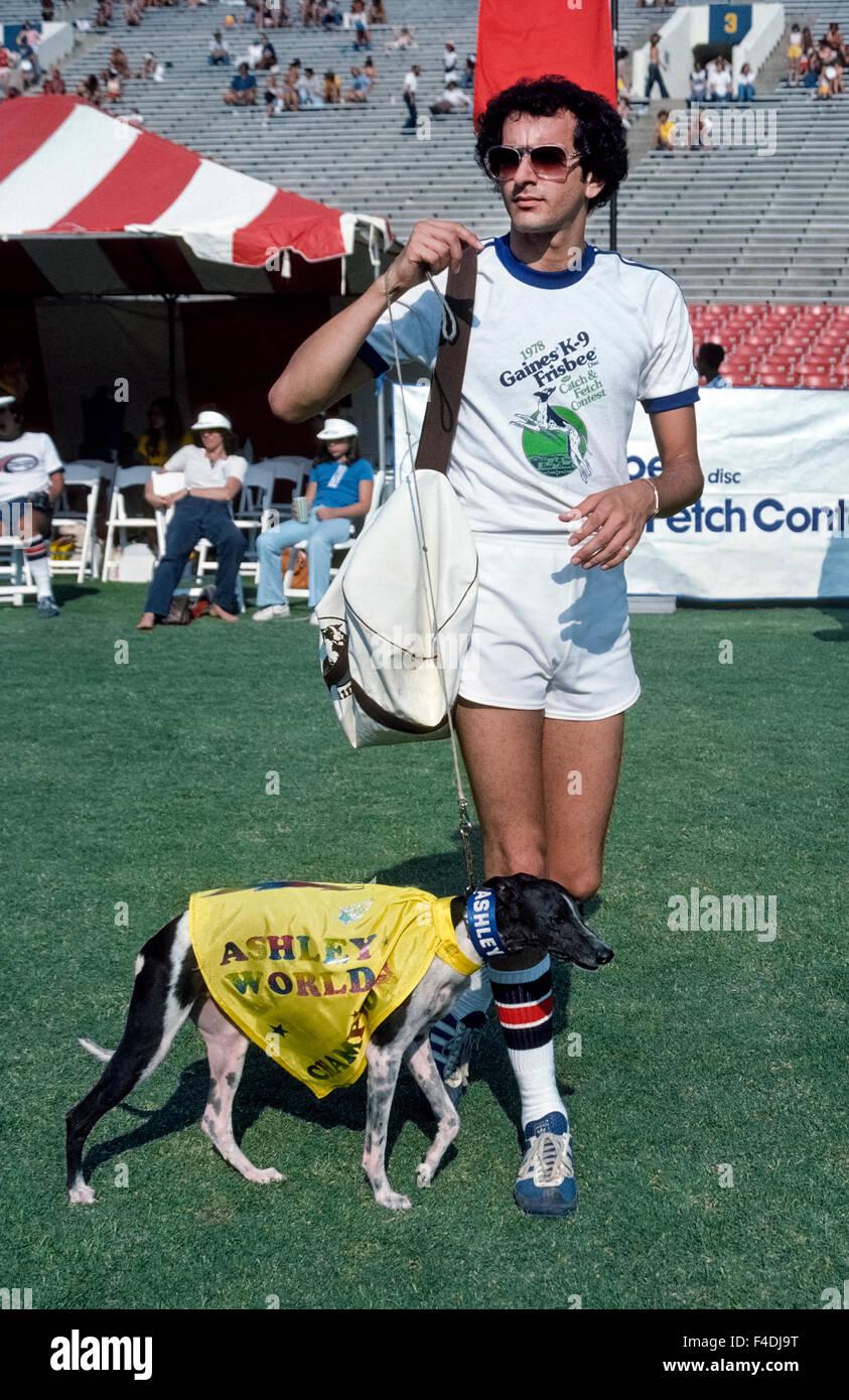 Il famoso disco-la cattura del cane Ashley Whippet prende al campo con il suo proprietario Alex Stein all annuale Frisbee cane World Championship tenutosi presso il Rose Bowl di Pasadena, California, Stati Uniti d'America. L'atletica cane potrebbe correre veloce come 35 miglia all'ora (56 km/h) e leap alta come 9 piedi (2,74 metri) per catturare i dischi volanti nella sua bocca. Ashley ha vinto i primi tre campionati del mondo che ha iniziato nel 1975, e un decennio più tardi il concorso è stato rinominato il Ashley Whippet Invitational in suo onore. Prima che egli morì nel 1985 all'età di 14, il cane eseguito anche nel Super Bowl e la Casa Bianca. Foto Stock