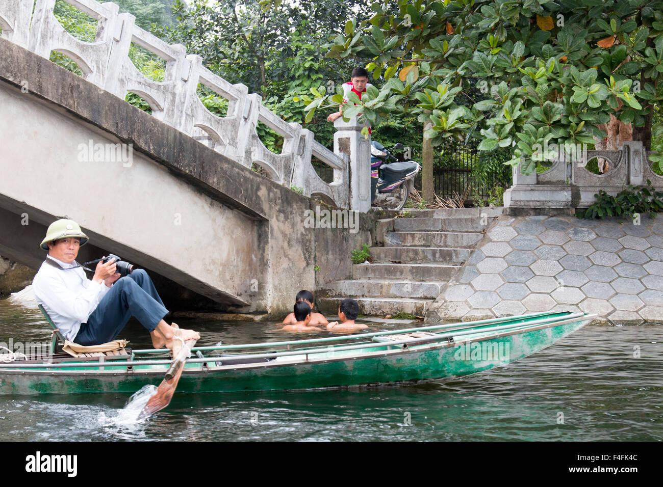Tre ragazzi nuotare bagnarsi nelle ONG dong fiume mentre l'uomo attende a fotografare i turisti in fila imbarcazioni,Ninh Immagini Stock