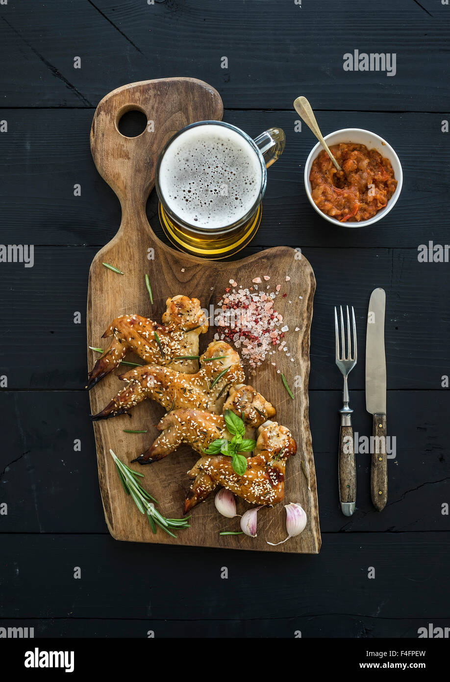 Alette di pollo fritte rustico che serve board, piccante salsa di pomodoro, erbe aromatiche e bicchiere di birra Immagini Stock