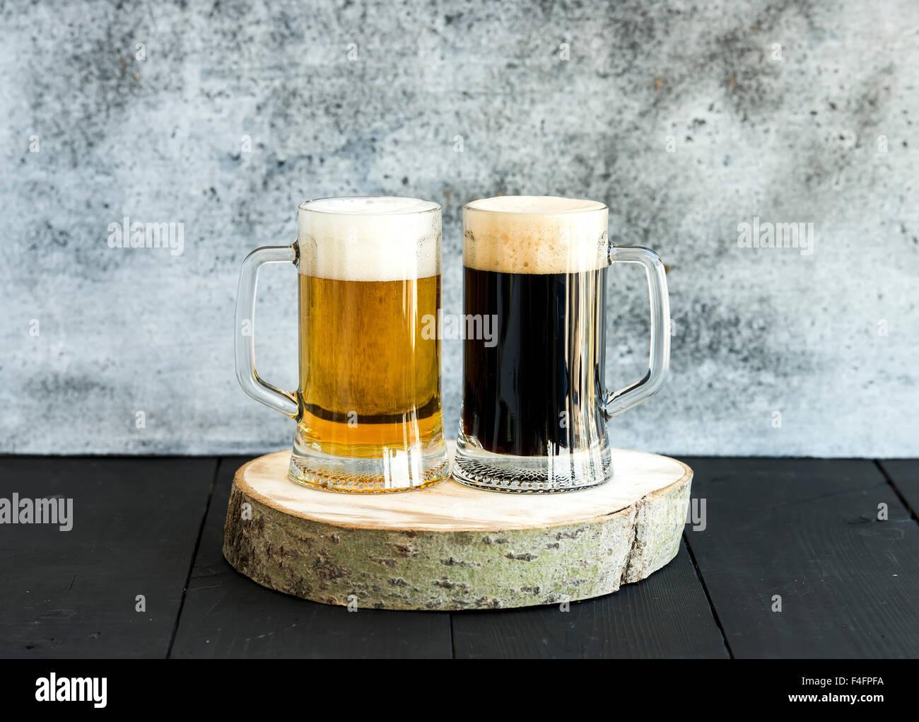 Luce e birra scura in tazze sulla tavola di legno, grunge sfondo Immagini Stock