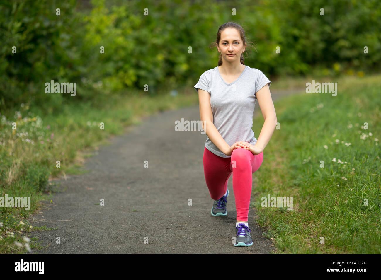 Giovane ragazza sportivo in fase di riscaldamento prima di fare jogging nel parco. Immagini Stock