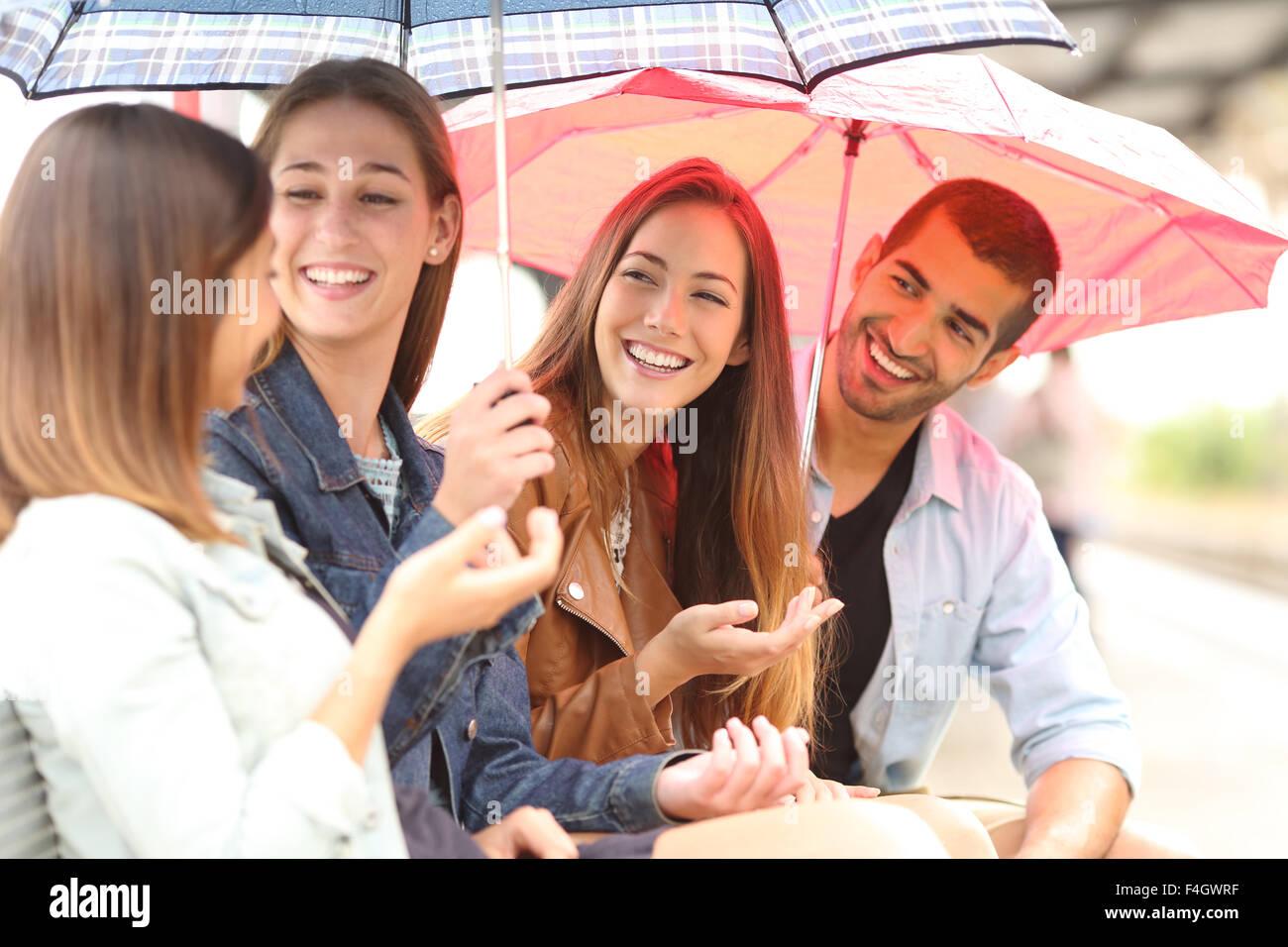 Quattro amici parlando all'aperto in un giorno di pioggia sotto gli ombrelloni in attesa in una stazione ferroviaria Immagini Stock