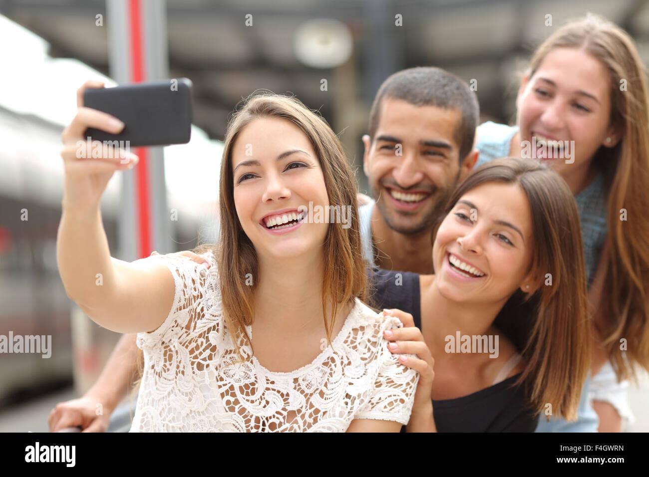 Il gruppo di quattro simpatici amici prendendo selfie con uno smart phone in una stazione ferroviaria in estate Immagini Stock
