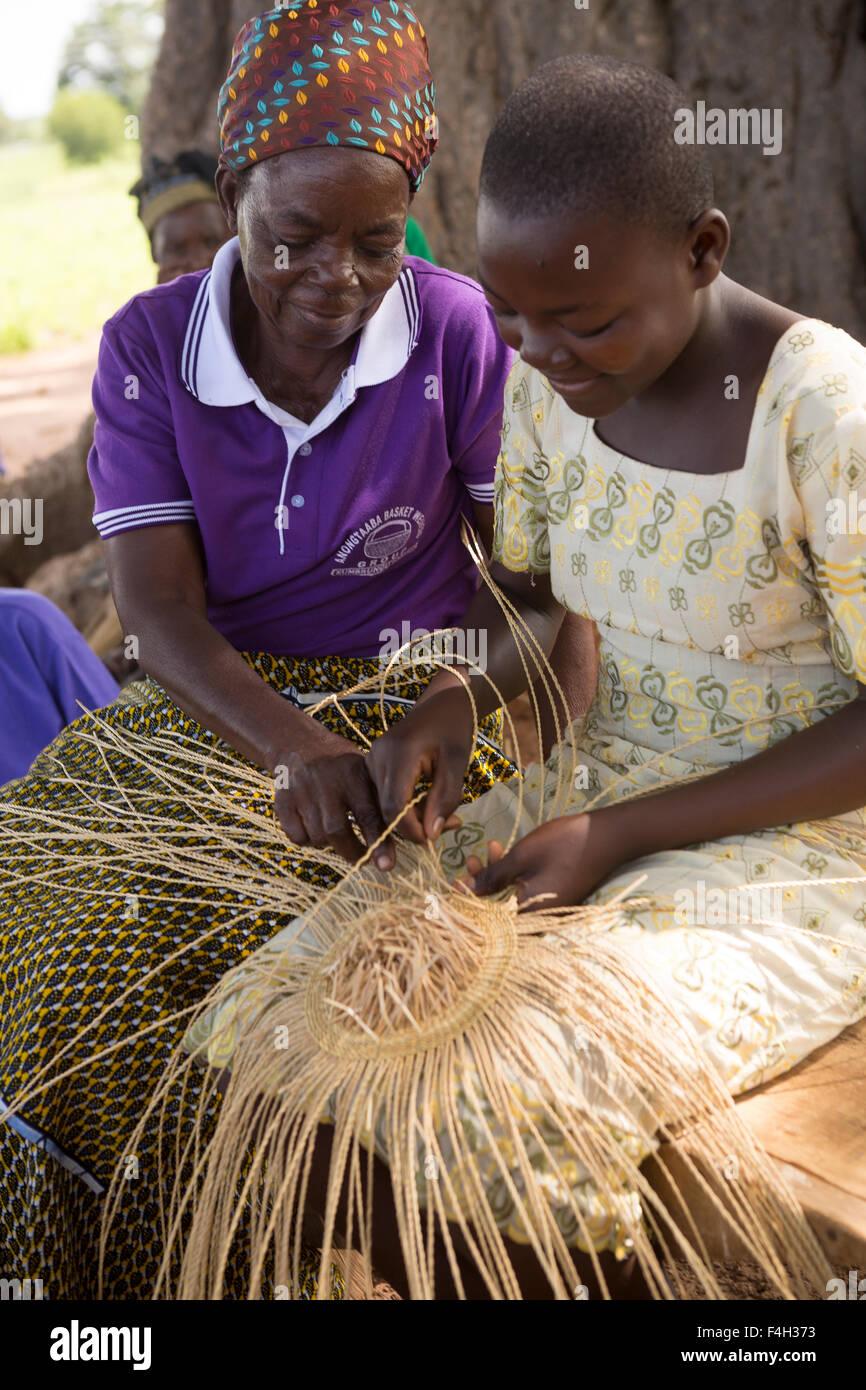 Il commercio equo e solidale, ornati in cesti di paglia sono tessute dalle donne del cestello Amongtaaba tessitori Immagini Stock