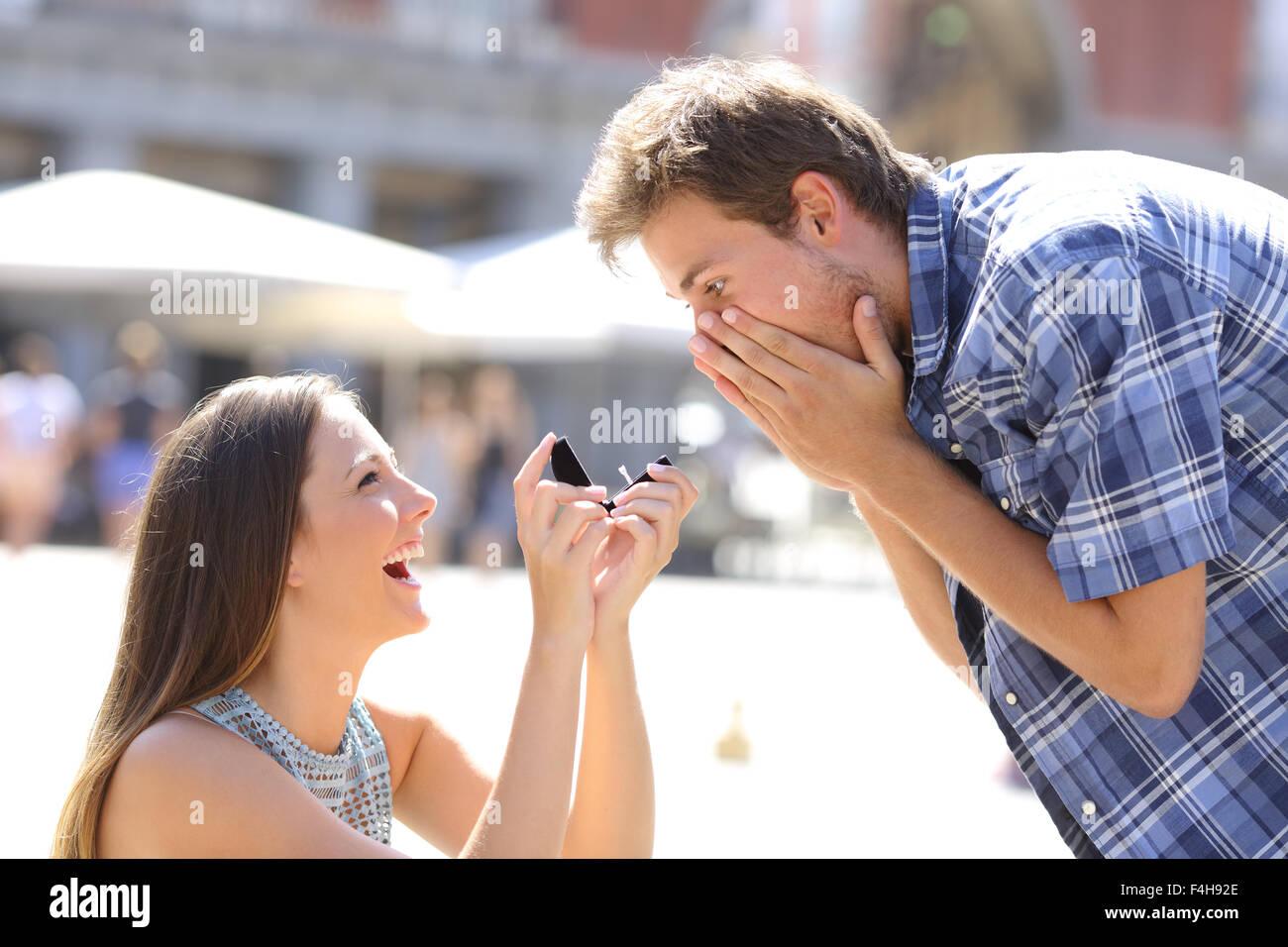 Proposta di una donna chiedendo a sposarsi con un uomo nel mezzo di una strada Immagini Stock