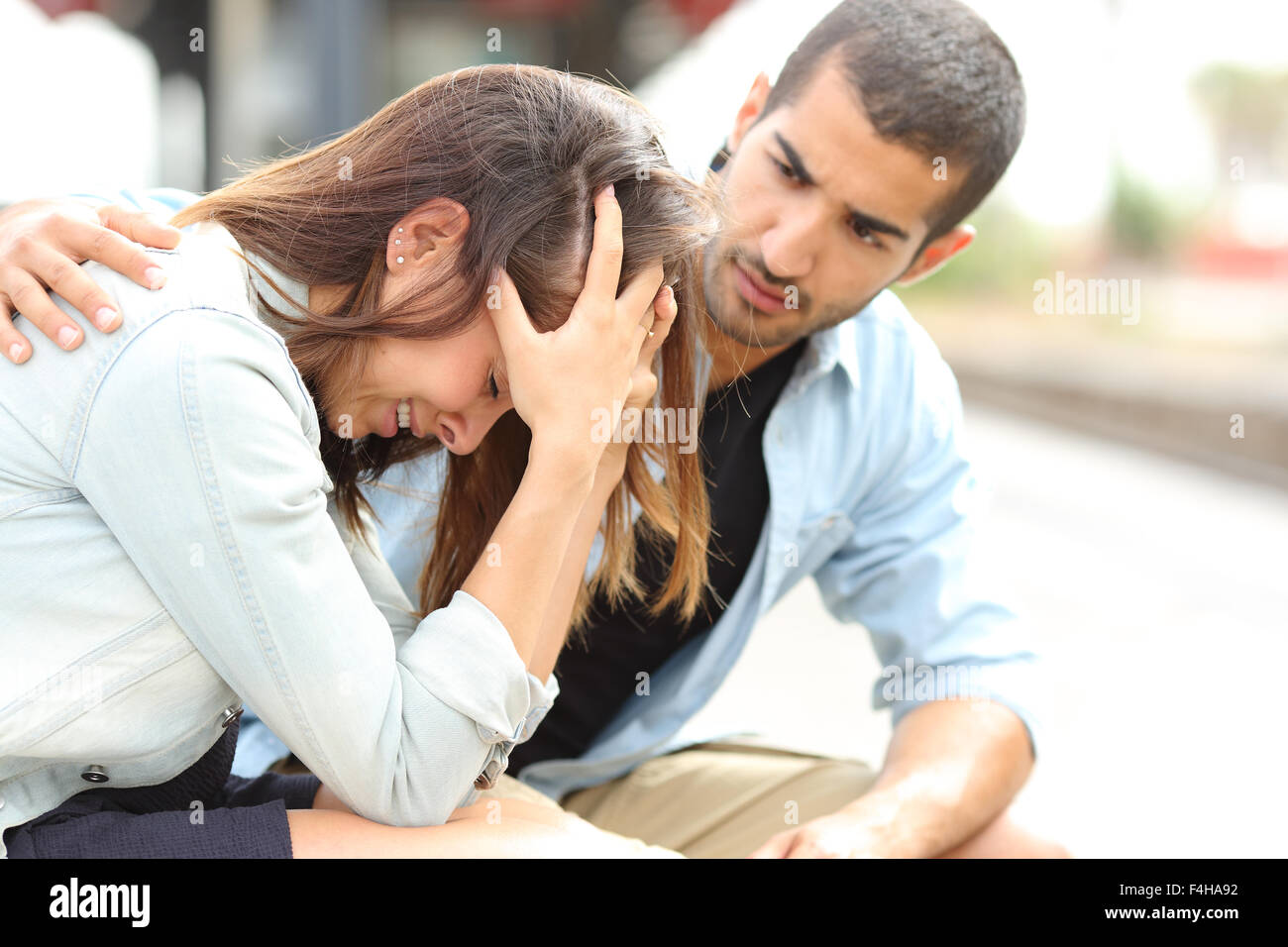 Vista laterale di un uomo musulmano consolante una triste ragazza caucasica lutto in una stazione ferroviaria Immagini Stock