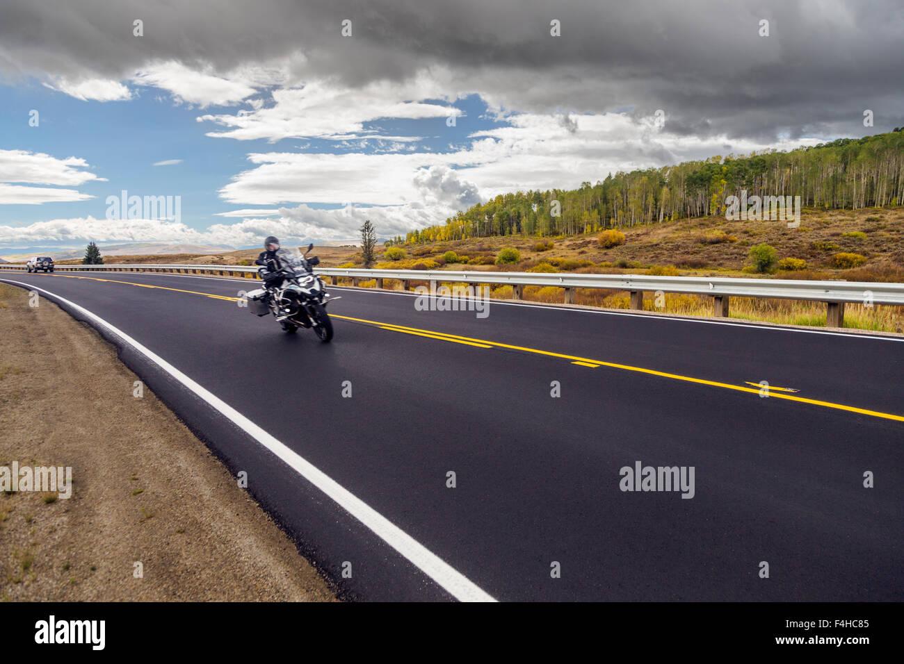Motociclo ciclista su strada asfaltata; Autostrada 40; North Central Colorado; USA Immagini Stock