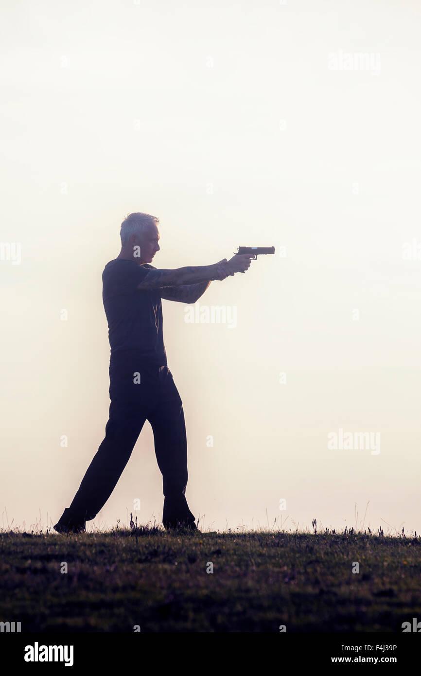 Silhouette di un uomo con una pistola Immagini Stock
