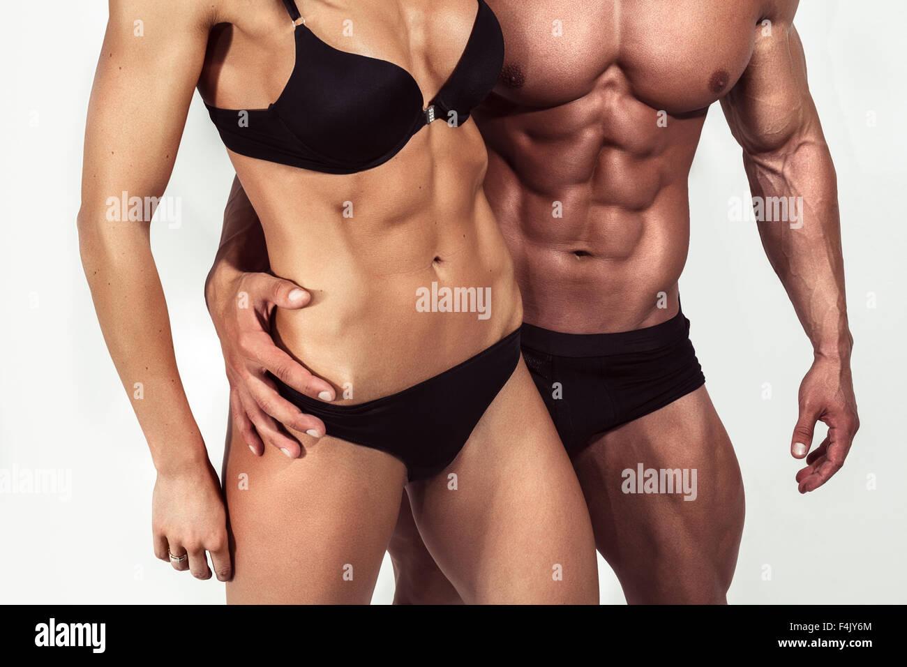 Bodybuilding. Uomo Forte e una donna in posa su sfondo bianco in studio Immagini Stock