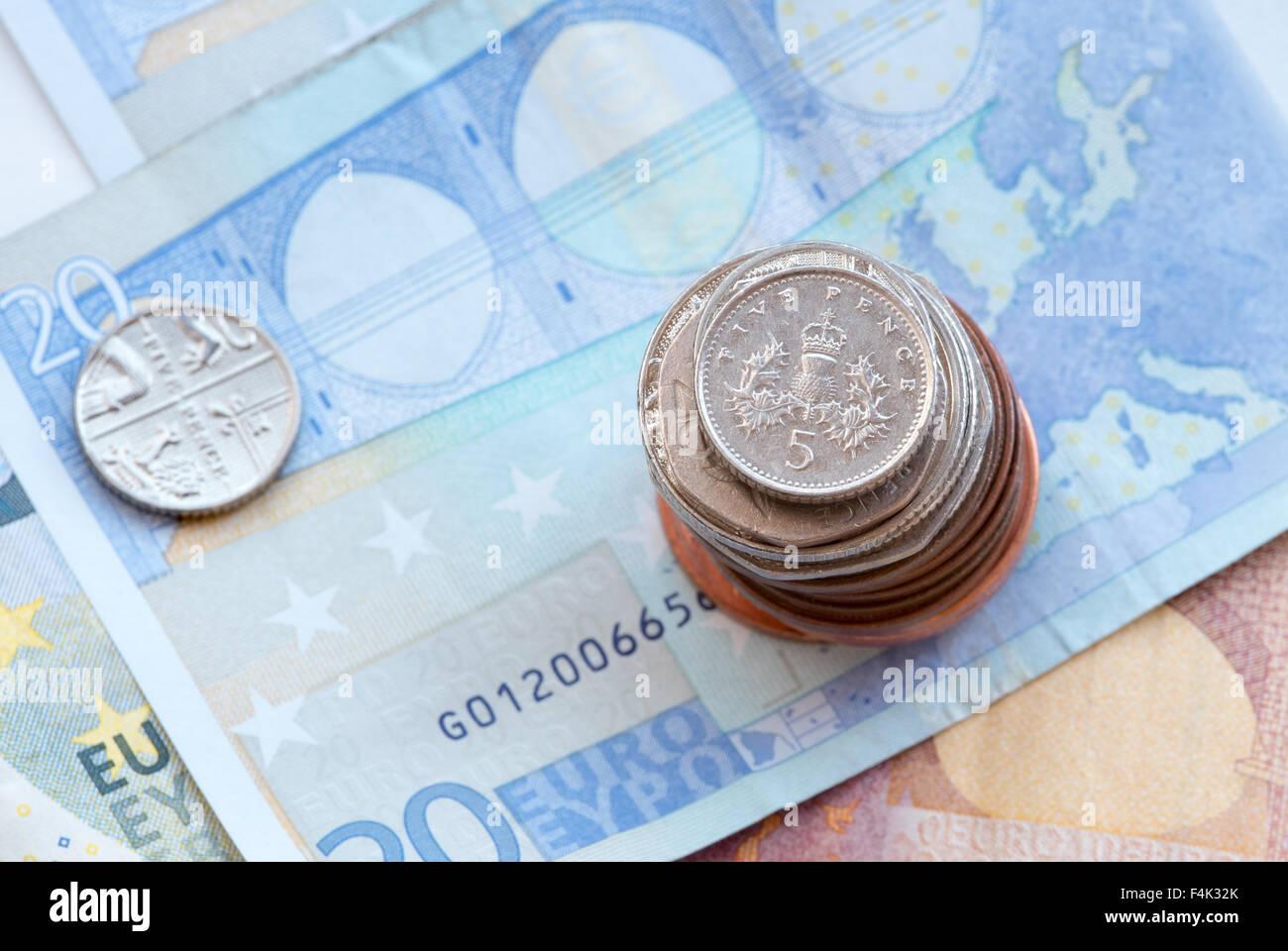 British cinque argento pence moneta su una pila di monete e venti banconote Foto Stock