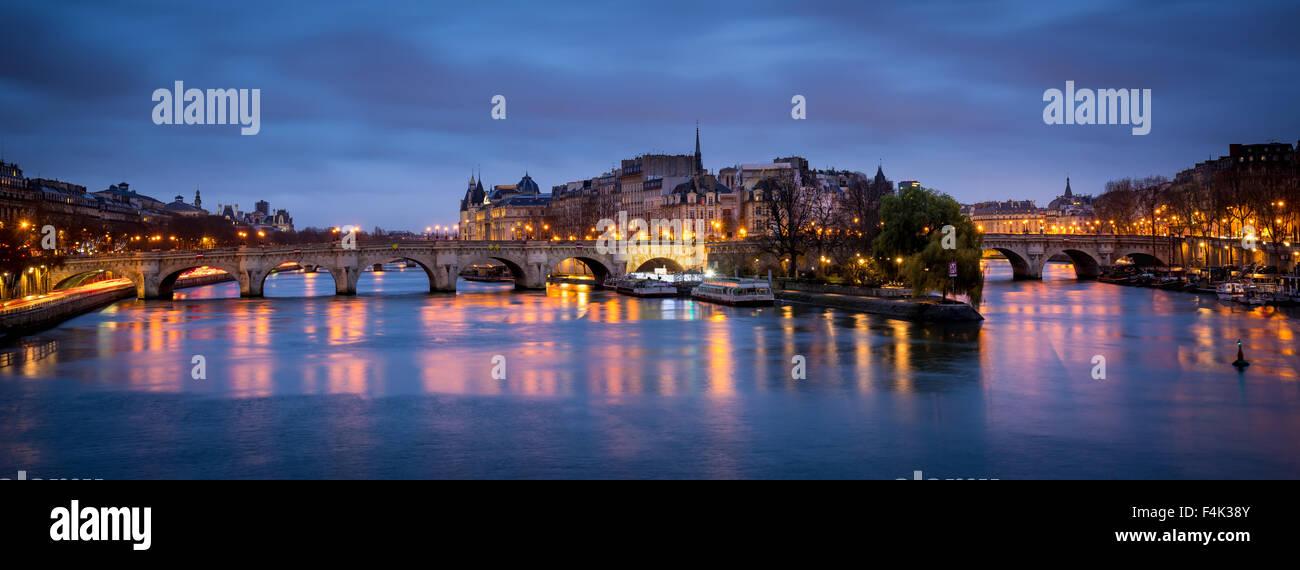 Ile de la Cite e Pont Neuf all'alba. La calma Senna riflette il mattino cielo nuvoloso e la strada si illumina. Immagini Stock